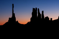 The sun rises over rock formations in Monument Valley, Utah.