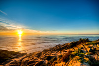 The sun sets over the Pacific Ocean at Sunset Cliffs in the Point Loma neighborhood of San Diego, CA.