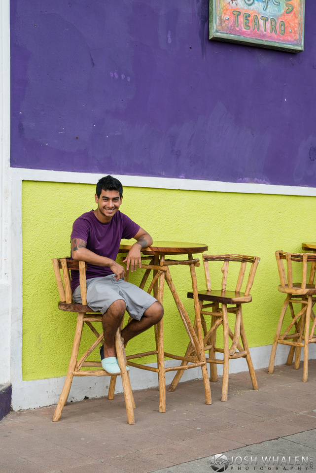 A young man sits out front of a cafe in Granada, Nicaragua.